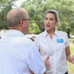 Gisela Triana (candidate for Justice, 3rd Court of Appeals, Place 6) visits with Steve Kirkland (Candidate for Supreme Court, Place 2) at the Kyle/Buda-Area Democrats Ice Cream Social on Aug. 5 at the Kyle City Square Park gazebo.  Photo by Christopher Paul Cardoza